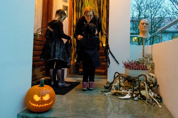 Homes offering treats signify this by placing a candle or ghostly objects outside their front ...