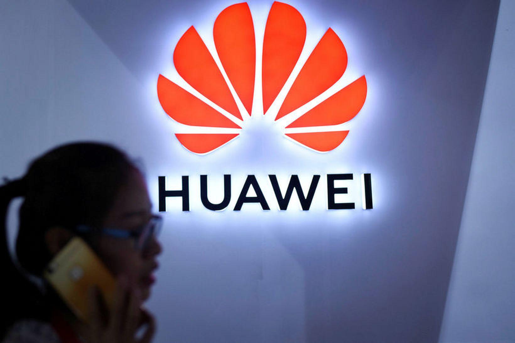 Kona notar síma sinn við merki Huawei í Peking.