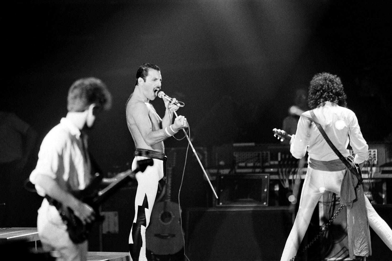 John Deacon, Freddie Mercury og Brian May á tónleikum í …