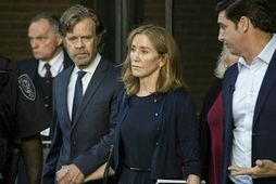 Actress Felicity Huffman, escorted by her husband William H. Macy (L), exits the John Joseph ...