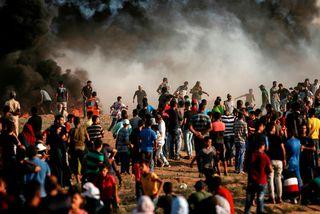 Palestínumenn brenna dekk við öryggisgirðinguna á Gaza í dag.