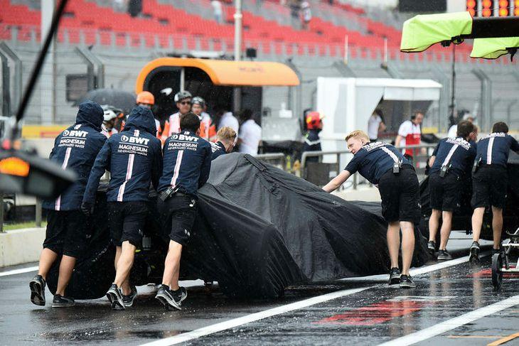 Regndúk var skellt yfir bíla Force India er þeir voru tilfærðir á lokaæfingunni.