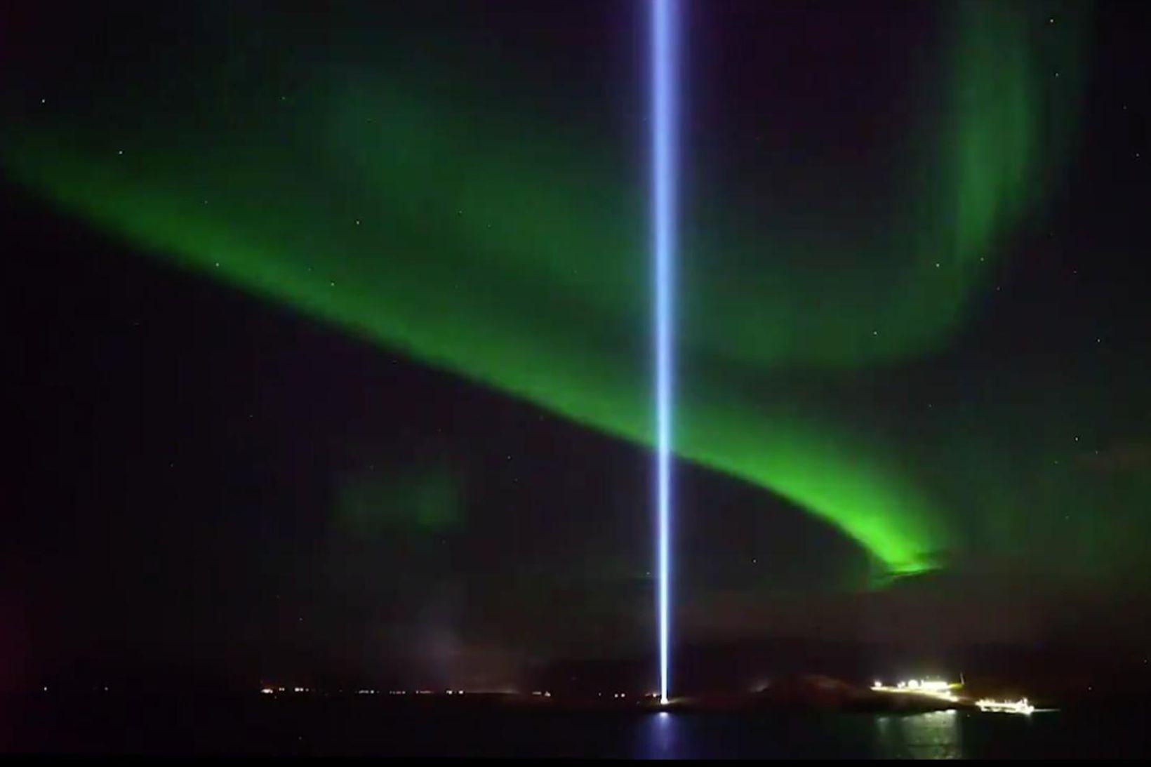 Friðarsúlan í Viðey og norðurljósin lýsa upp himininn.