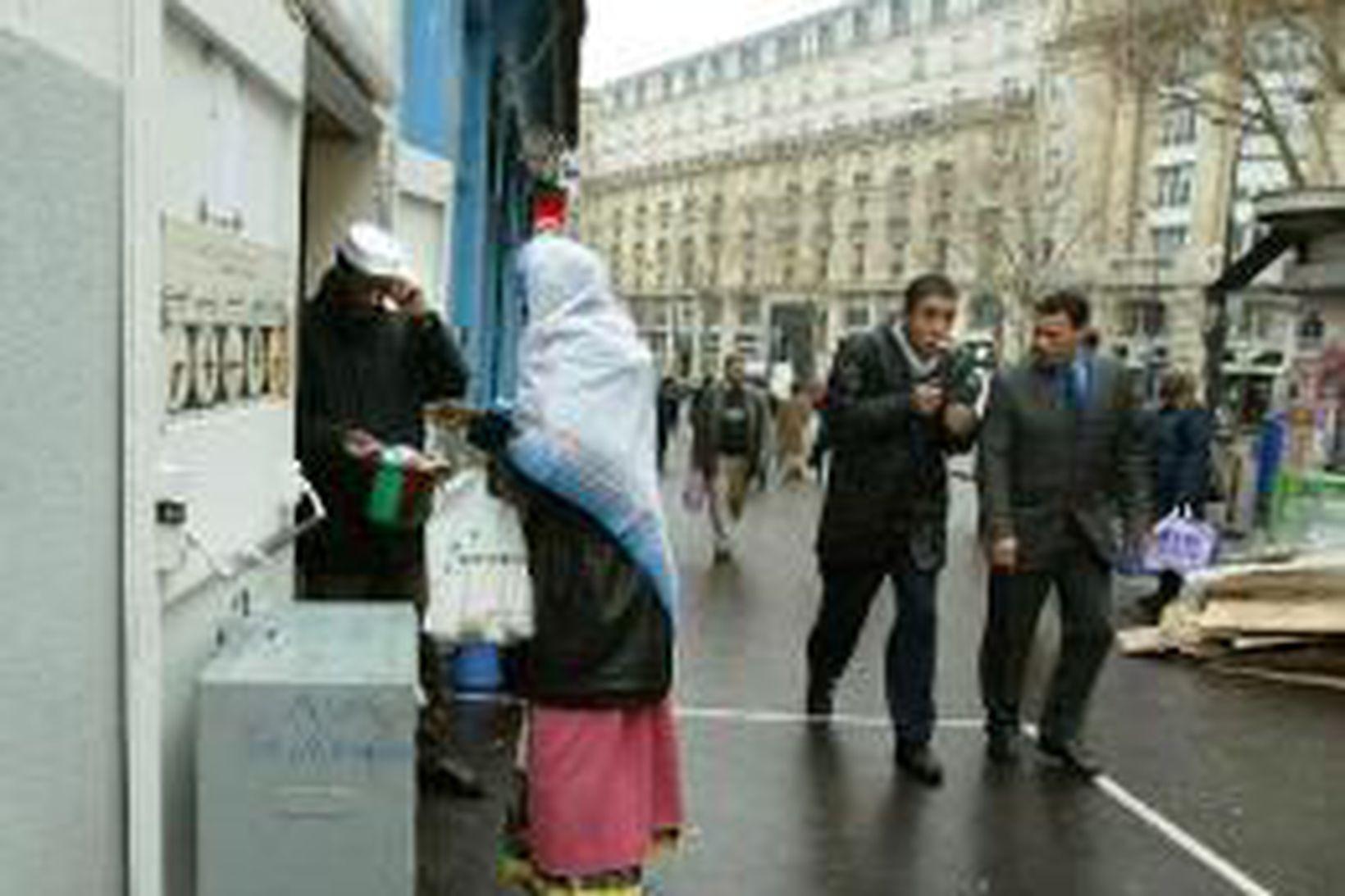 Múslimsk kona með höfuðblæju við mosku í París.