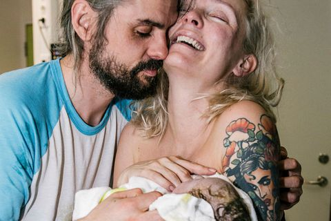 Andrea and her boyfriend holding their newborn son.