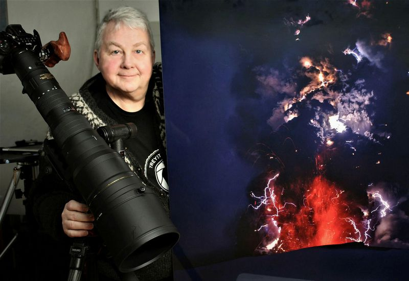 Ragnar Th. Sigurðsson is ready with the camera. He stands beside a photo he took of the 2010 eruption in Eyjafjallajökull.