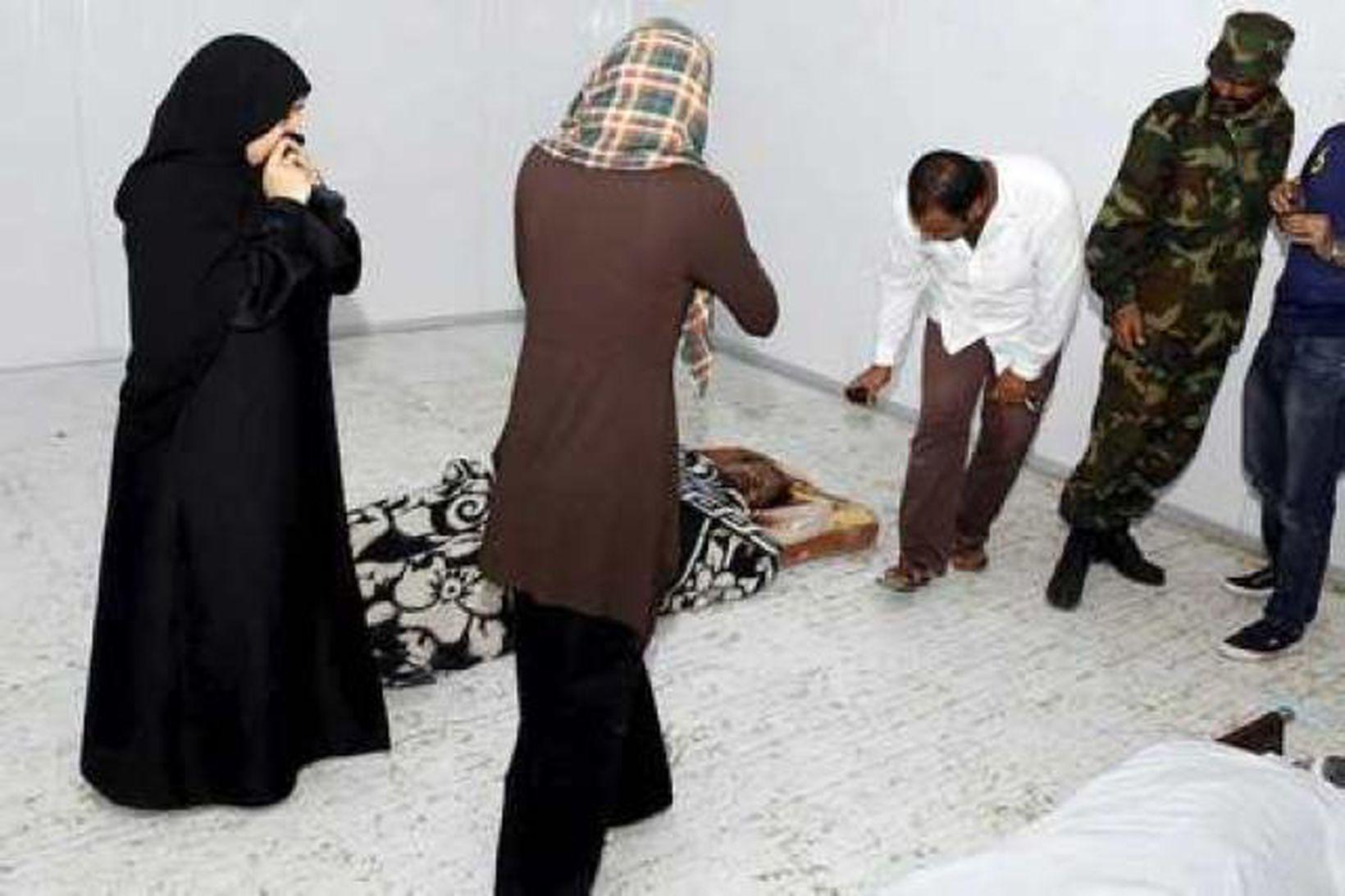 Fólk tekur myndir af líki Gaddafis sem liggur enn í …