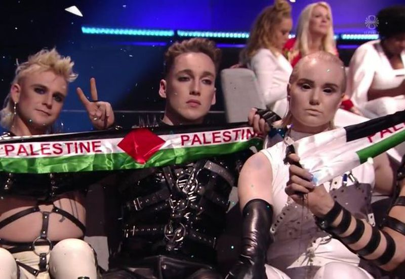 Hatari band members, waving a banner in the colors of the Palestinian flag.