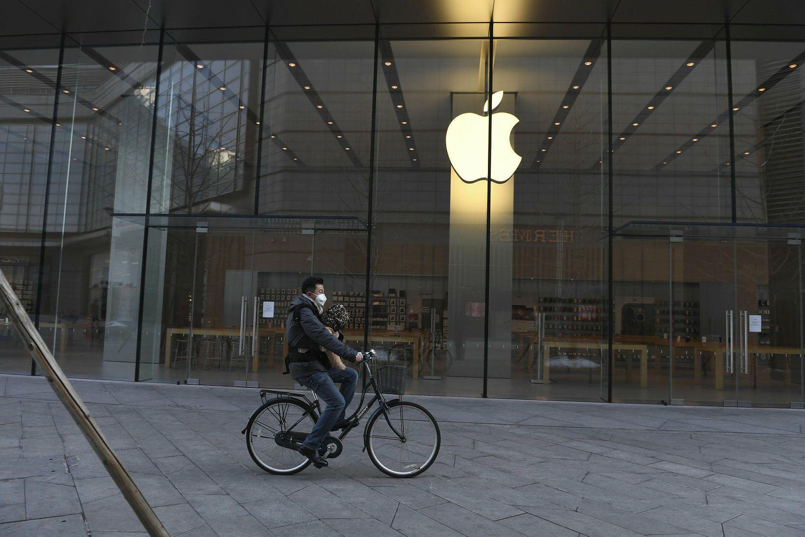 Maður hjólar fram hjá Apple-búðinni í Peking fyrr í þessum …