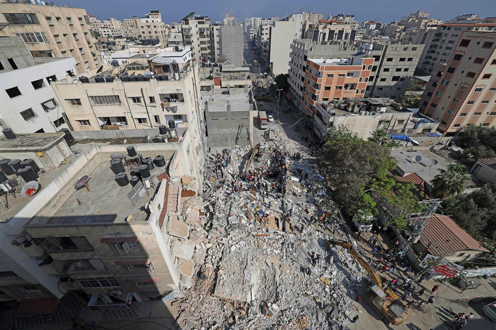 Björgunarsveitir leita í rústum byggingar í Rimal-hverfinu í Gaza eftir …
