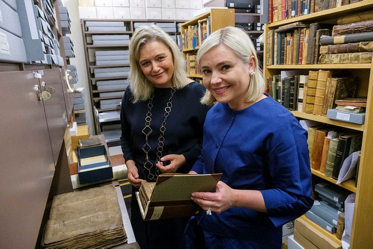 Education Minister Lilja Alfreðsdóttir, right, looks at an old manuscript at the Árni Magnússon Institute …