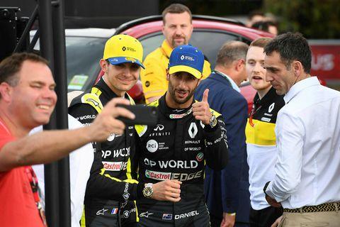 Daniel Ricciardo (með bláa húfu) og Esteban Ocon (með gula húfu) stilla sér upp fyrir …