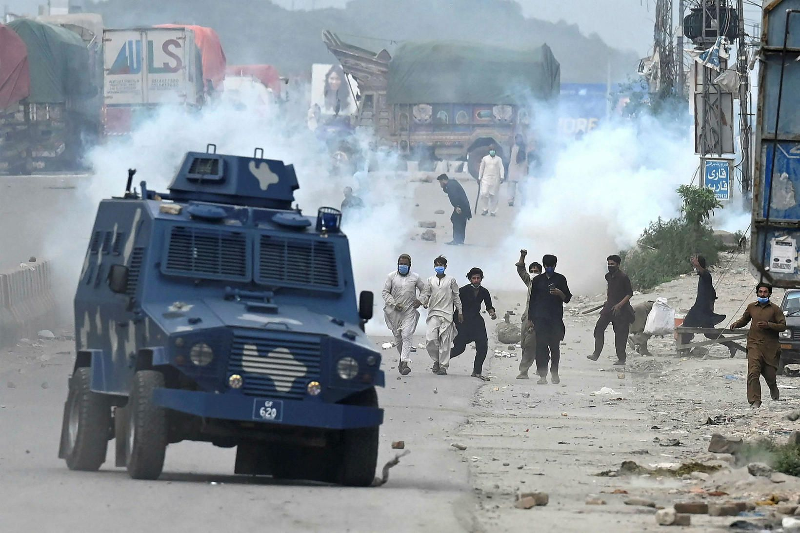 Stuðningsmenn TLP-flokksins í Pakistan kasta seinum að brynvörðum bíl lögreglunnar …