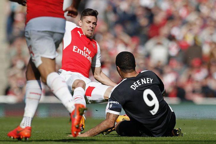 Gabriel Paulista, leikmaður Arsenal tæklar Troy Deeney, leikmann Watford, í leik liðanna í dag.