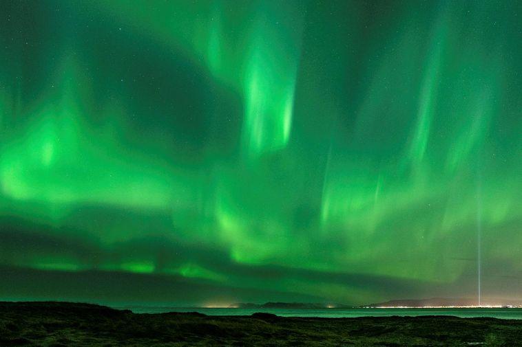 Looking toward Reykjavík from Vatnsleysuströnd beach, Saturday night. Light from the Imagine Peace Tower on …
