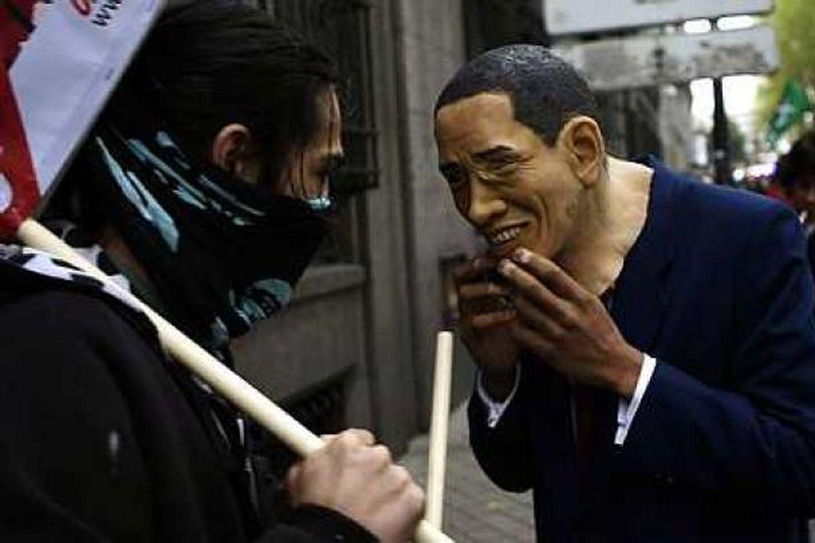 Mótmælandi á Spáni ber grímu með mynd af Barack Obama …