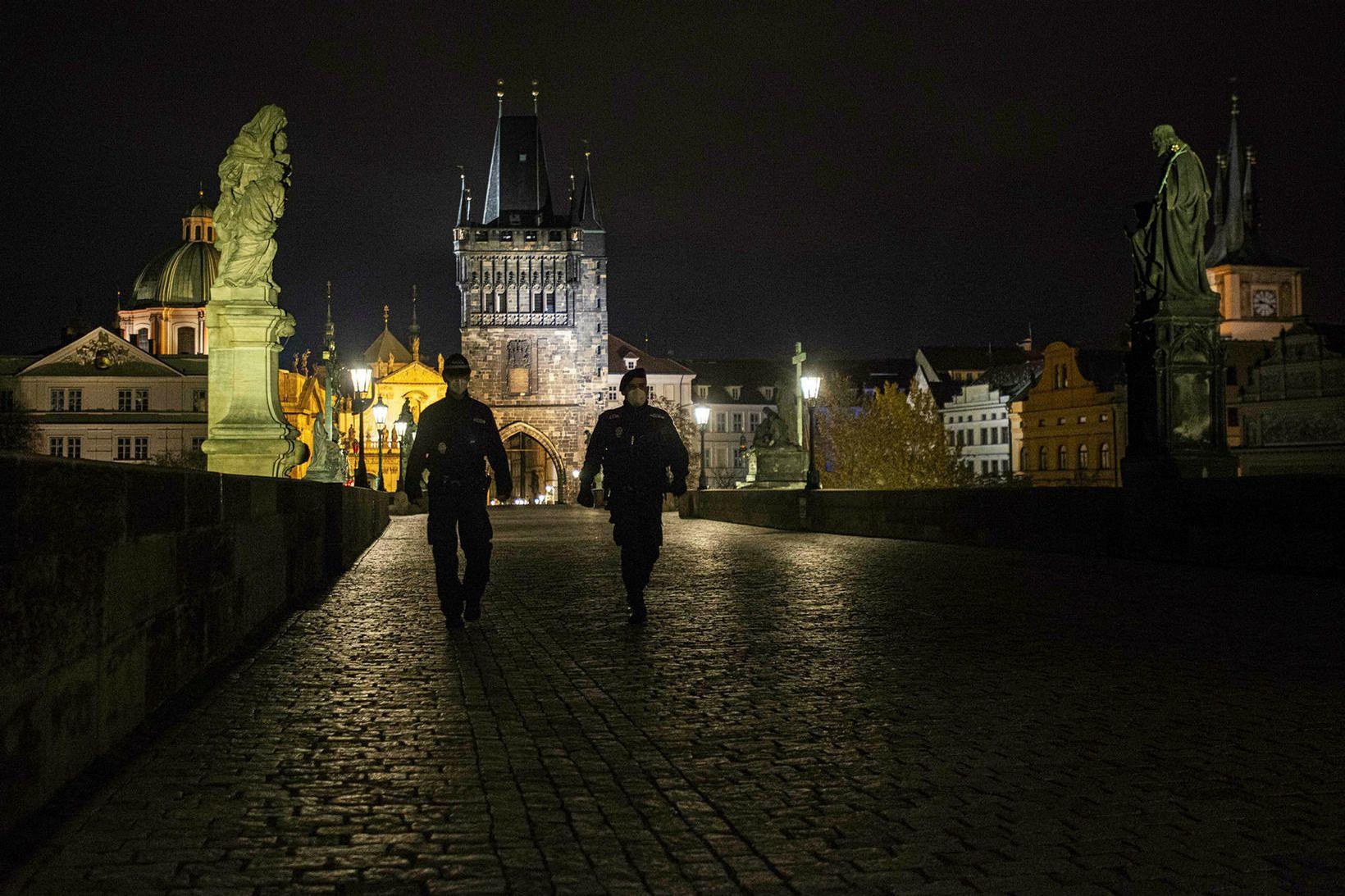 Lögreglumenn á gangi yfir Charles-brúna í Prag.