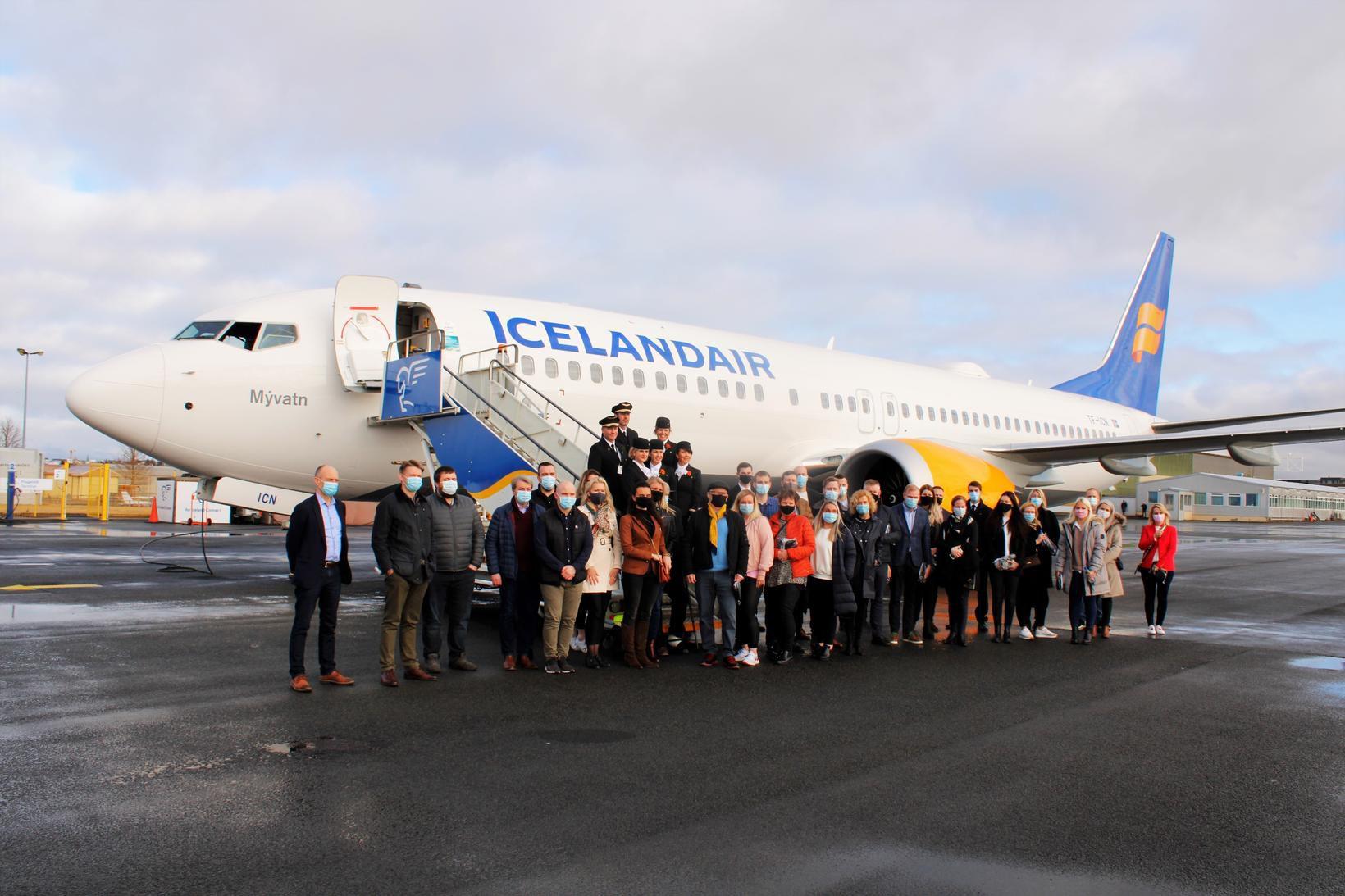 Farþegar í fluginu við vélina eftir lendingu á Reykjavíkurflugvelli í …