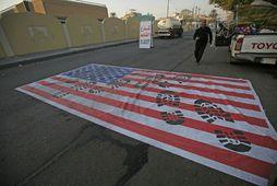 Fáni Bandaríkjanna sést hér vanvirtur á götu í Bagdad í dag. Innan Íraks eru skiptar …
