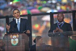 Milljónir manna fylgdust með Barrack Obama, forseta Bandaríkjanna, og Thamsanqa Jantjie við minningarathöfnina um Nelson …