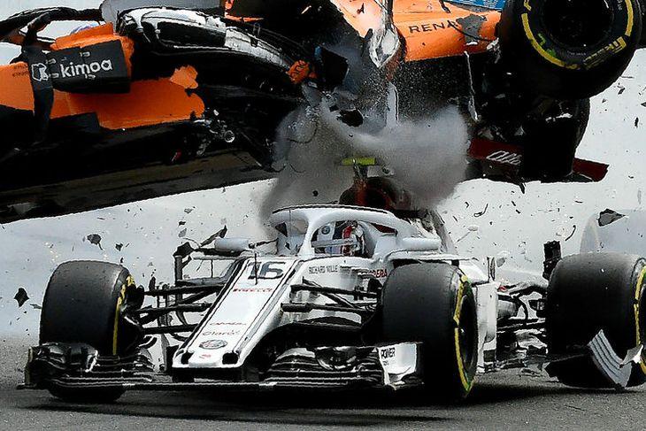 McLarenbíll Fernando Alonso flýgur með brambolti yfir Sauberbíl Charles Leclerc í hópárekstrinum í fyrstu beygjunni ...