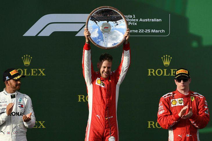 Sebastian Vettel með sigurskjöldinn á verðlaunapallinum í Melbourne.
