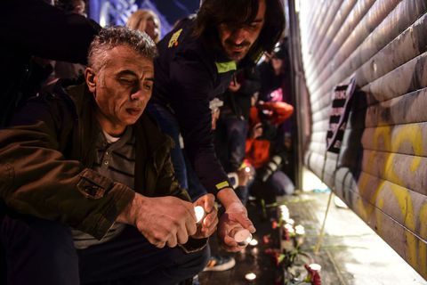 People light candles at the site of the blast.