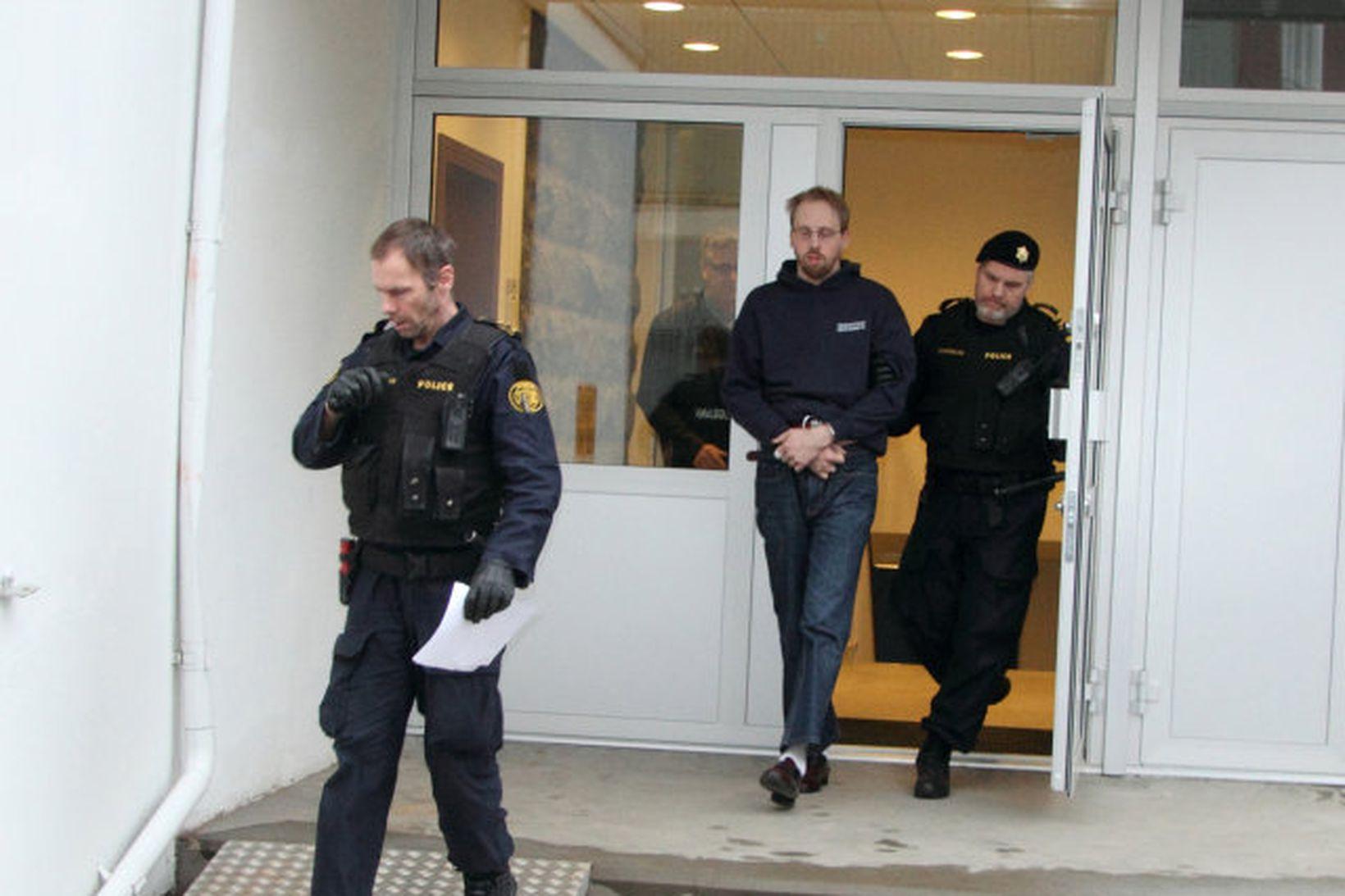 Guðgeir Guðmundsson í fylgd lögreglumanna.