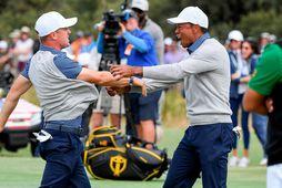 Justin Thomas og Tiger Woods fagna sínum sigri í Melbourne í nótt.