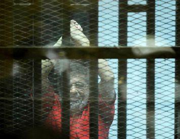 Mohamed Morsi, fyrrverandi forseti Egyptalands bak við rimlanna í réttarsalnum í Karíó. Lífstíðardómur yfir Morsi ...