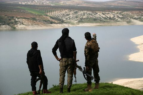 . Members of the armed Kurdish forces looking at lake Maydanki in Afrin, Syria.