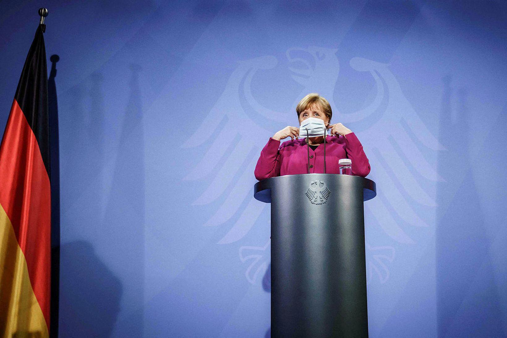 Angela Merkel Þýskalandskanslari setur á sig sóttvarnagrímu á blaðamannafundi 25. …