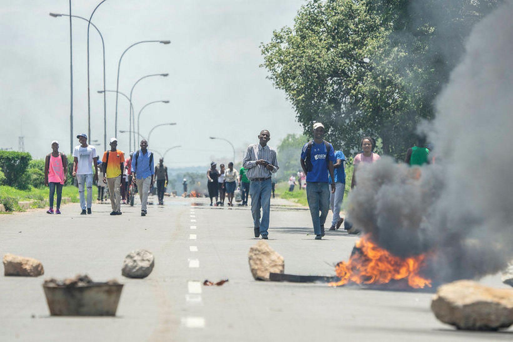 Hópar fólks ganga fram hjá vegartálma í Bulawayo í dag.