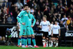 Lionel Messi hnugginn er leikmenn Valencia fagna í bakgrunni.