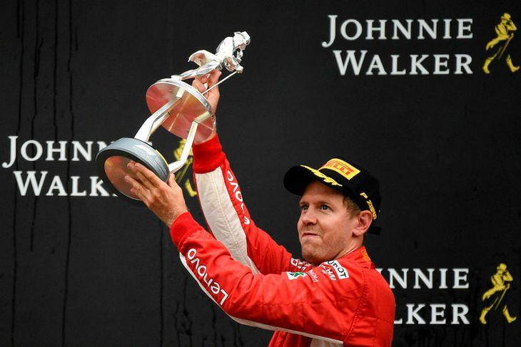 Sebastian Vettel hampar verðlaunagrip sínum í Spa; styttu af viskíkónginum Jóni á röltinu.