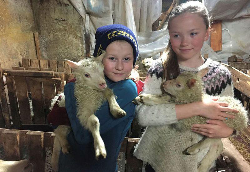Kría and Jóhanna, holding the lambs Blíða and Blær.