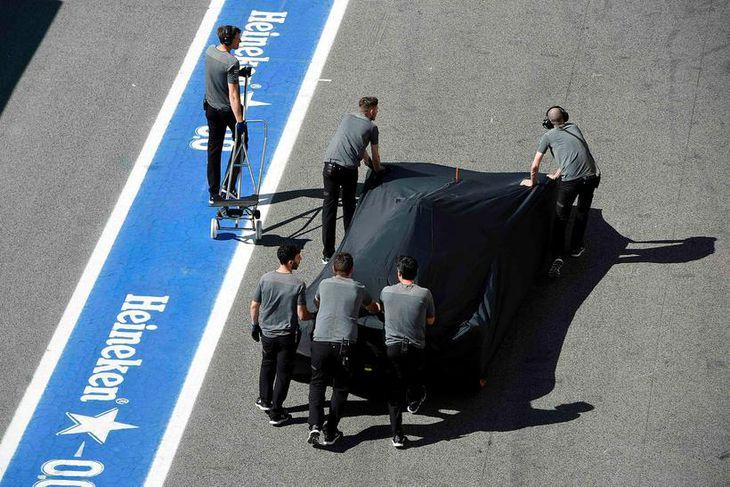 Vélvirkjar Fernando Alonso sækja bíl hans sem stoppaði í brautinni vegna olíuleka í morgun.