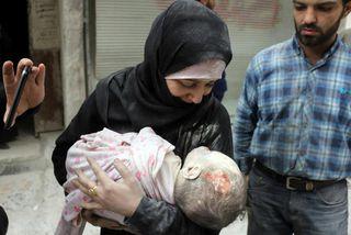 Kona með lík barnsins síns í Aleppo.