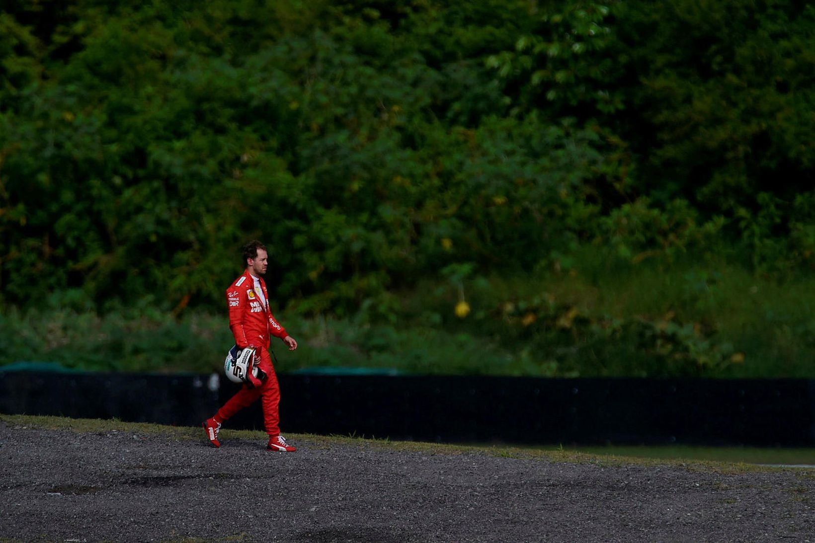 Sebastian Vettel gengur af vettvangi eftir árekstur við liðsfélaga sinn, …