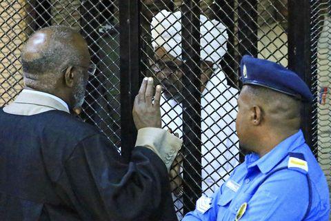 Omar al-Bashir situr í búri sakborgnings á réttarhöldunum sem fóru fram í dag.