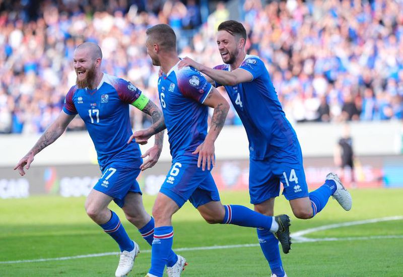 Aron Einar Gunnarsson, left, and Kári Árnason, right, celebrate with Ragnar Sigurðsson, after his goal.