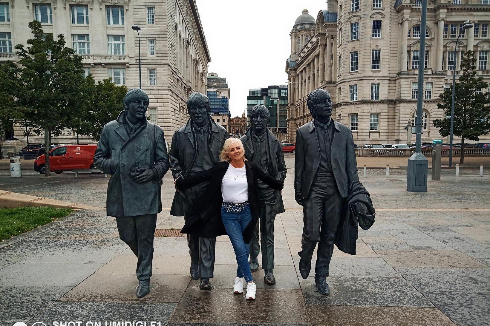 Linda Baldvinsdóttir með Bítlastyttunum í Liverpool.