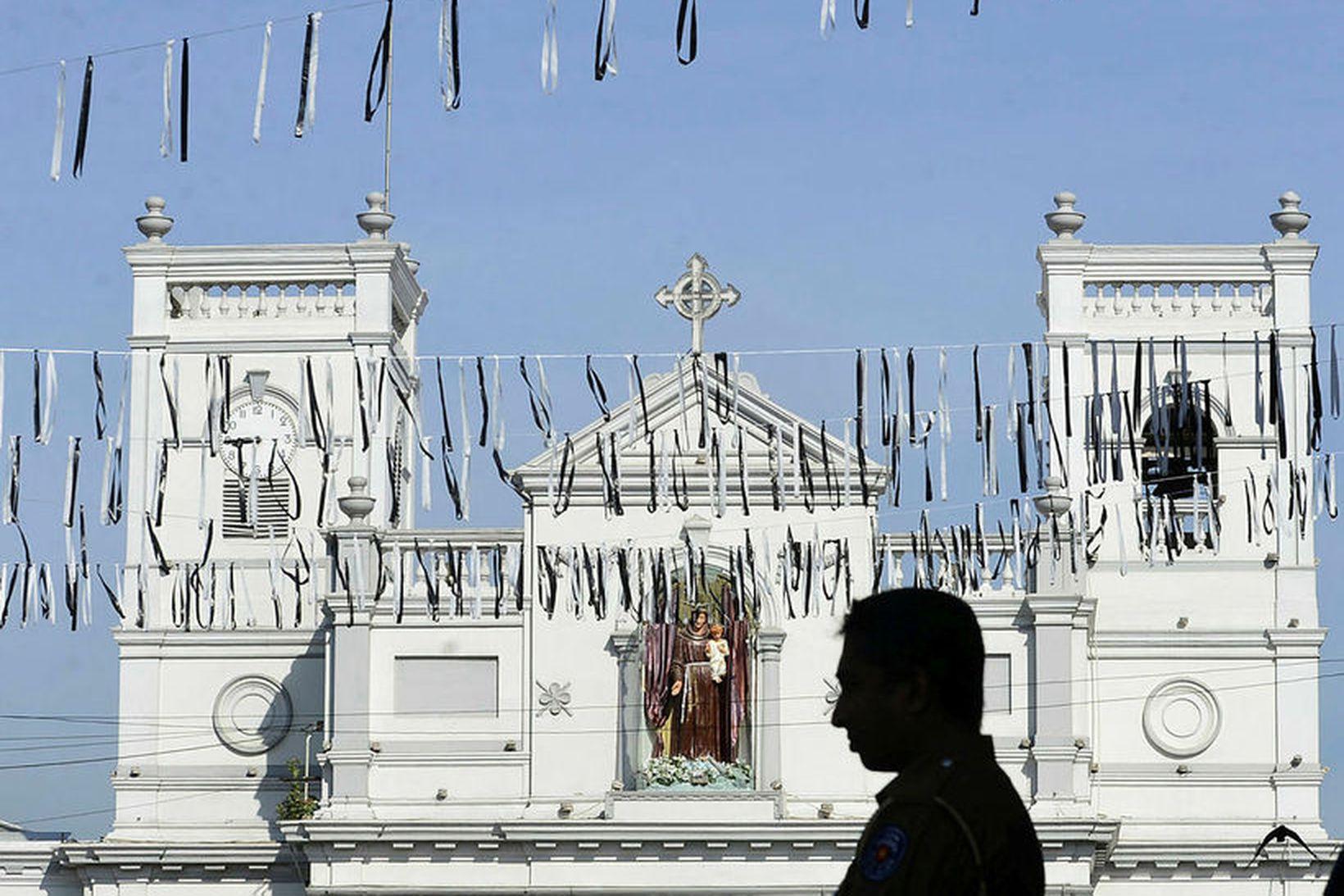 Maður stendur fyrir utan kirkju í Colombo, sem var á …