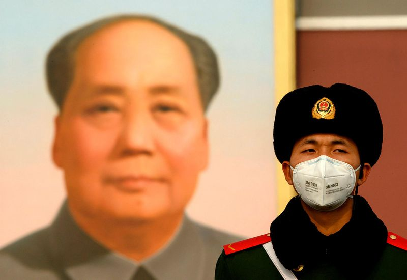A soldier in Beijing, in front of a poster of Mao Zedong.