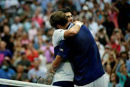 Novak Djokovic og Daniil Medvedev fallast í faðma eftir viðureignina í gærkvöldi.