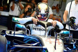 Lewis Hamilton fær sér sæti í Mercedesbílnum fyrir tímatökuna í Silverstone.