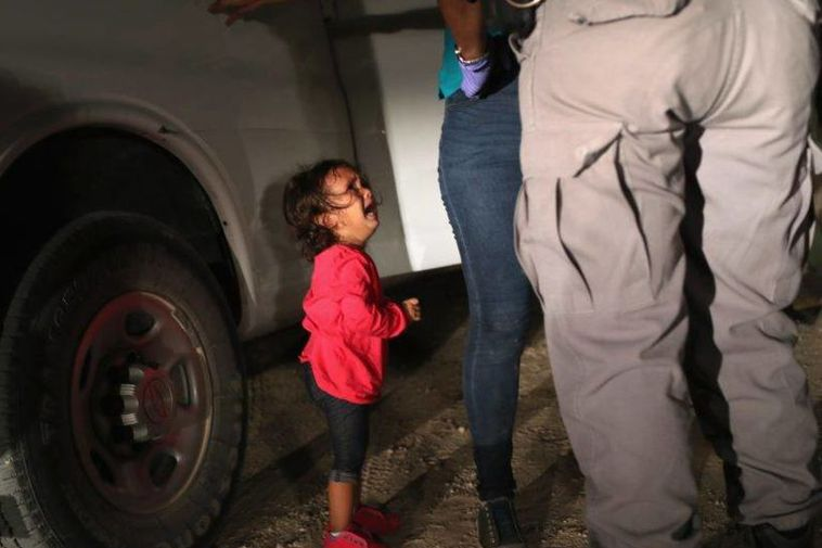 A two year old girl cries at the US border