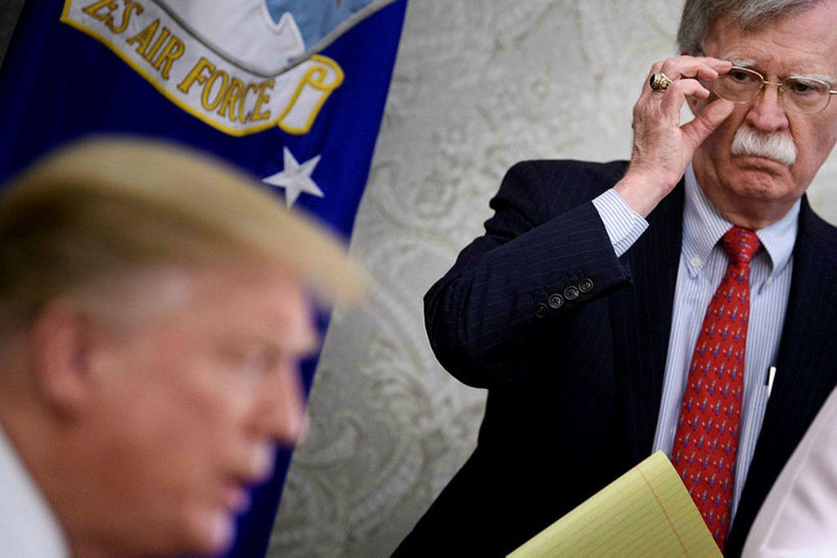 John Bolton (t.h.) fyrrverandi þjóðaröryggisráðgjafi Trump, hlýðir hér á forsetann …
