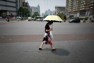 Kona gengur undir sólhlíf í Peking.