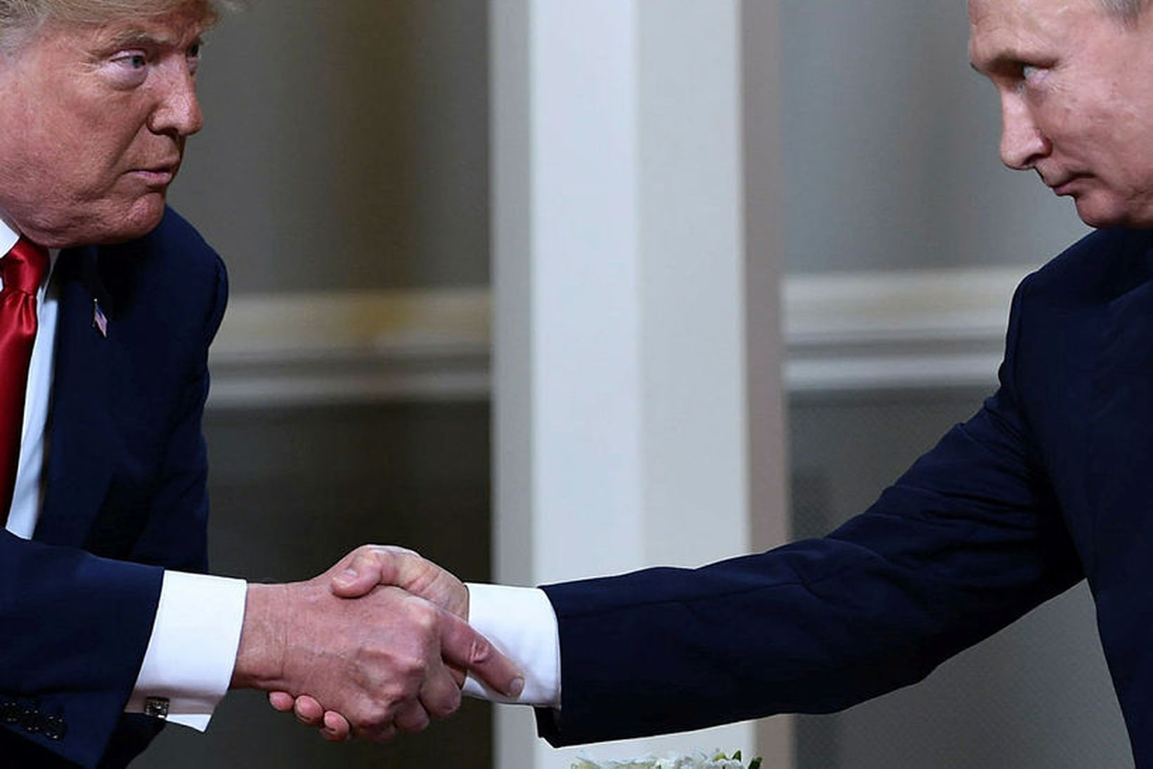 Donald Trump Bandaríkjaforseti og Vladimír Pútín Rússlandsforseti takast í hendur …